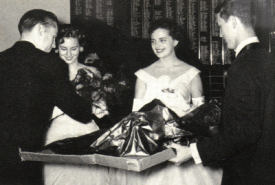Pi Kappa Phi members Jack McCain and Jerry Payne presenting Beta Omicron chapter Rose Queens Peggy Kerr (Plunkett) and Clois (Warner) Witt with presents.